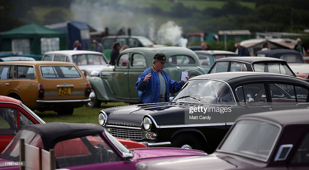 People gather around classic cars being shown in the showground at the Cornish Steam and Country Fair at the Stithians Showground on August 16, 2013 near Penryn, England. The annual show, now in 58th year, is one of Cornwall's largest outdoor events and is one of the UK's most popular and respected steam rallies.