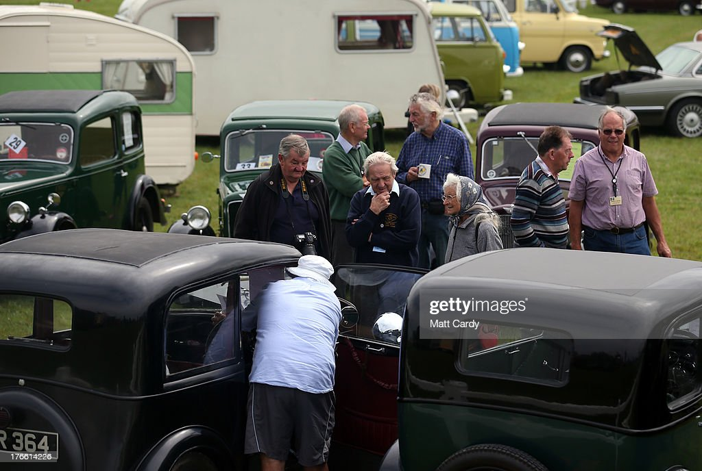 People gather around classic cars being shown in the showground at the Cornish Steam and Country Fair at the Stithians Showground on August 16, 2013 near Penryn , England. The annual show, now in 58th year, is one of Cornwall's largest outdoor events and is one of the UK's most popular and respected steam rallies.