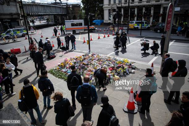 People gather around floral tributes on London Bridge by the scene of the June 3rd terror attacks on June 6 2017 in London England Seven people were...