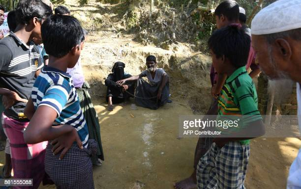 People gather around Rohingya refugee Ali Hussain as he is restrained by his sister with a metal chain at Balukhali refugee camp in Ukhia district on...