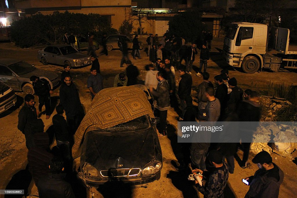 People gather around the car of a police officer after it exploded in the eastern Libyan city of Benghazi late on January 15, 2013. A car bomb killed a police officer, an official said, the latest violence to hit the cradle of the 2011 revolt that ousted dictator Moamer Kadhafi. AFP PHOTO/Abdullah DOUMA