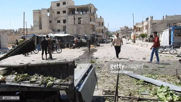 People gather around the damaged site after the war crafts belonging to the Assad regime forces carried out airstrikes on the Khan Shaykhun town of...