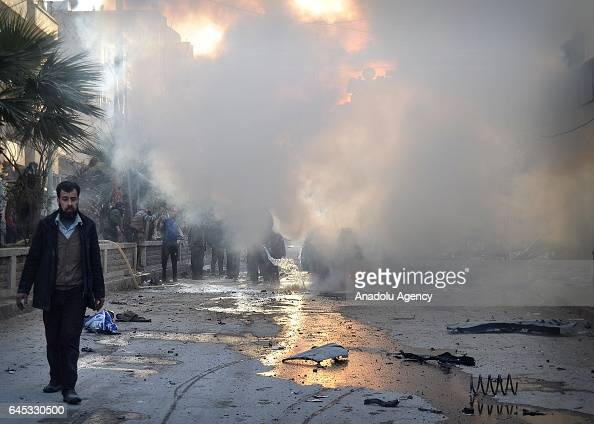 People gather around the fire at the impact site after Assad Regime's airstrike over civilians in residential areas of Ariha town of Idlib Syria on...