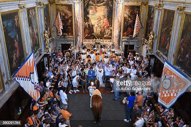 People gather around the horse called Remistrio as it receives the blessing at the San Giovannino della Staffa church in Siena in Tuscany on August...