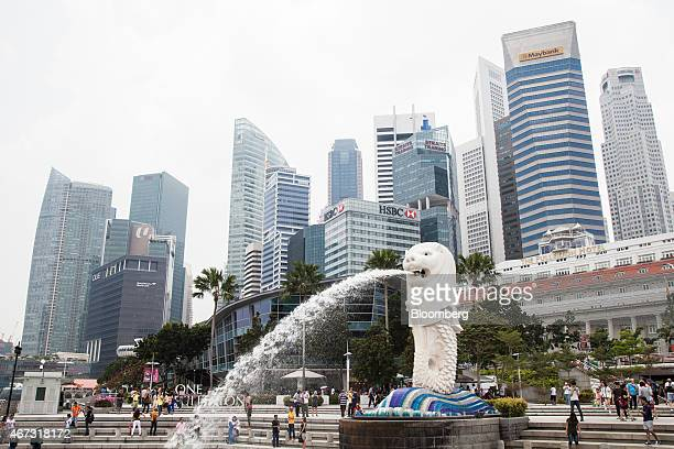 People gather around the Merlion statue at the Marina Bay waterfront as commercial building stand in the background in Singapore on Sunday March 22...
