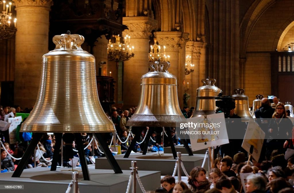 People gather around the new bells of Notre-Dame de Paris Cathedral during their blessing mass on February 2, 2013 in Paris. The biggest among the nine new bells has been made in the Dutch Royal Eijbouts foundry in Asten. Baptised 'Marie,' it weighs 6 tons and plays a G sharp note (sol diese). AFP PHOTO / FRANCOIS GUILLOT