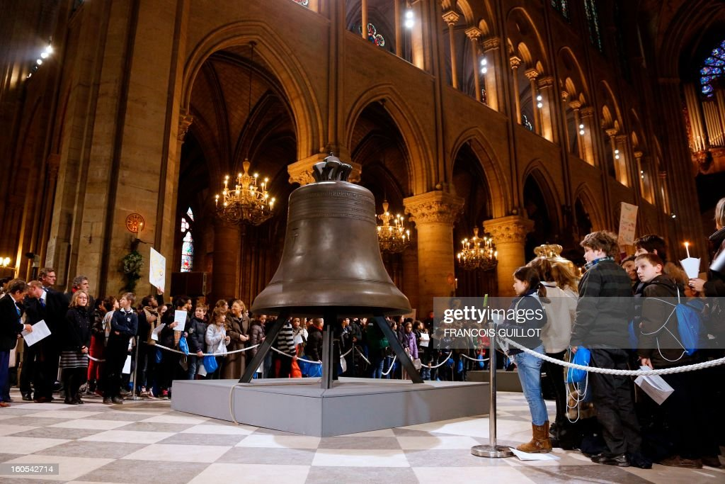 People gather around the new bells of Notre-Dame de Paris Cathedral to attend their blessing during a mass on February 2, 2013 in Paris. This bell, the biggest among the nine new ones, has been made in the Dutch Royal Eijbouts foundry in Asten. Baptised 'Marie,' it weighs 6 tons and plays a G sharp note (sol diese).