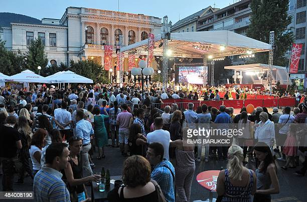 People gather around the red carpet area in front of National Theatre in Sarajevo on August 14 few hours before the grand opening ceremony of the...