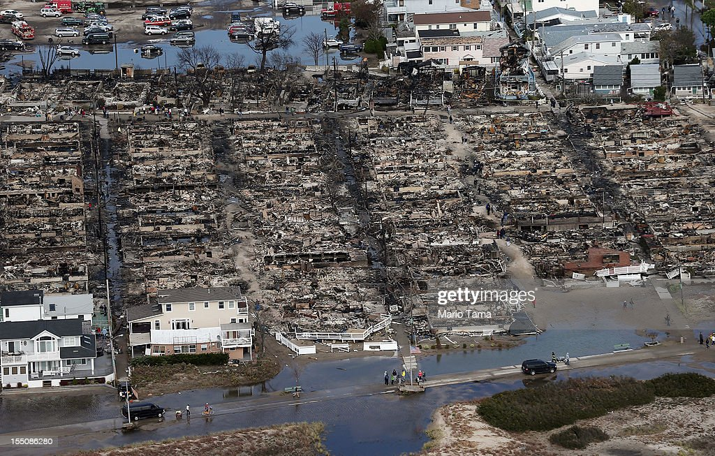 People gather around the remains of burned homes after Superstorm Sandy on October 31 2012 in the Breezy Point neighborhood of the Queens borough of...