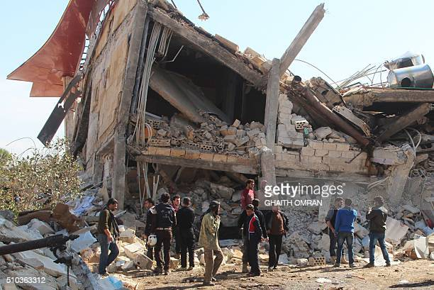 People gather around the rubble of a hospital supported by Doctors Without Borders near Maaret alNuman in Syria's northern province of Idlib on...