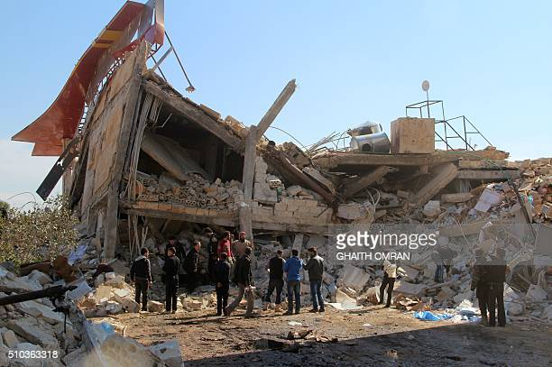 TOPSHOT People gather around the rubble of a hospital supported by Doctors Without Borders near Maaret alNuman in Syria's northern province of Idlib...