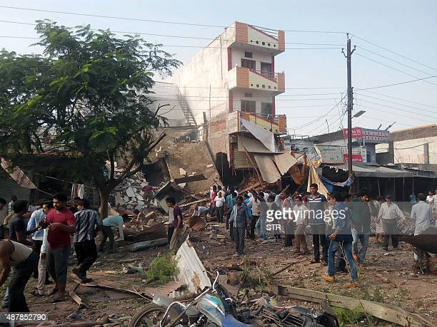 People gather around the site of an explosion at a restaurant in Jhabua district in the central Indian state of Madhya Pradesh on September 12 2015...