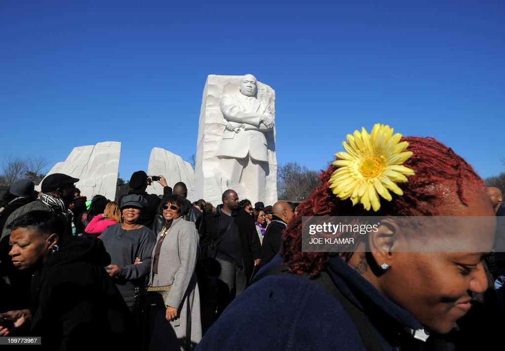 People gather around the statue of civil rights leader Martin Luther King, Jr. at the MLK Memorial on the occasion of Martin Luther King Day on January 20, 2013 in Washington. King is best known for his role in the advancement of civil rights using nonviolent civil disobedience. AFP PHOTO / JOE KLAMAR
