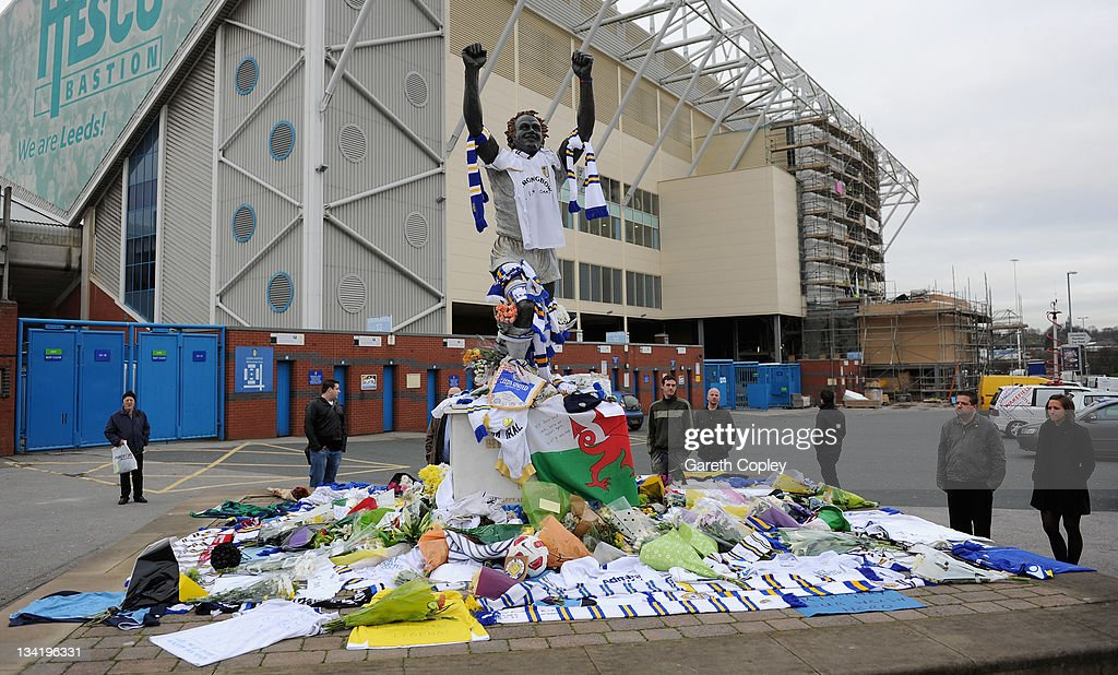 People gather around the tributes left at the Billy Bremner statue outside Elland Road football ground in memory of former player Leeds United Gary Speed on November 28, 2011 in Leeds, England. Wales Manager Gary Speed, 42, was found dead on November 27, 2011 in Cheshire, England.