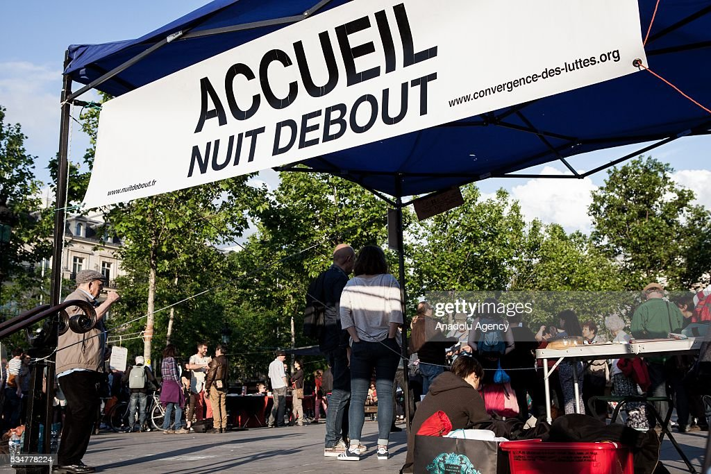 People gather around the welcoming stall on the Place de la Republique during the Global Debout meeting 'Nuit Debout' ('The Night awake' or Up all night') in Paris, France on May 27, 2016.