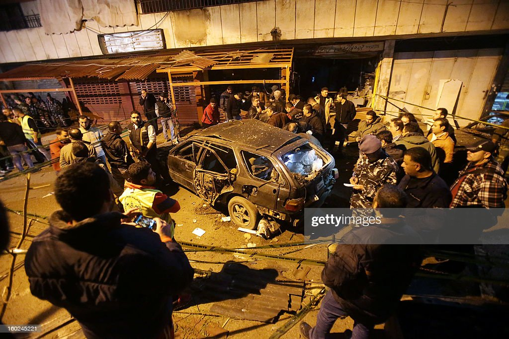 People gather around the wreckage of a car after a bomb placed under it exploded in a Shiite Muslim southern suburb of Beirut late on January 28, 2012, without causing casualties, a security source said. 'A bomb exploded under a car in Hay al-Sellom, causing only material damage,' the source told AFP on condition of anonymity.