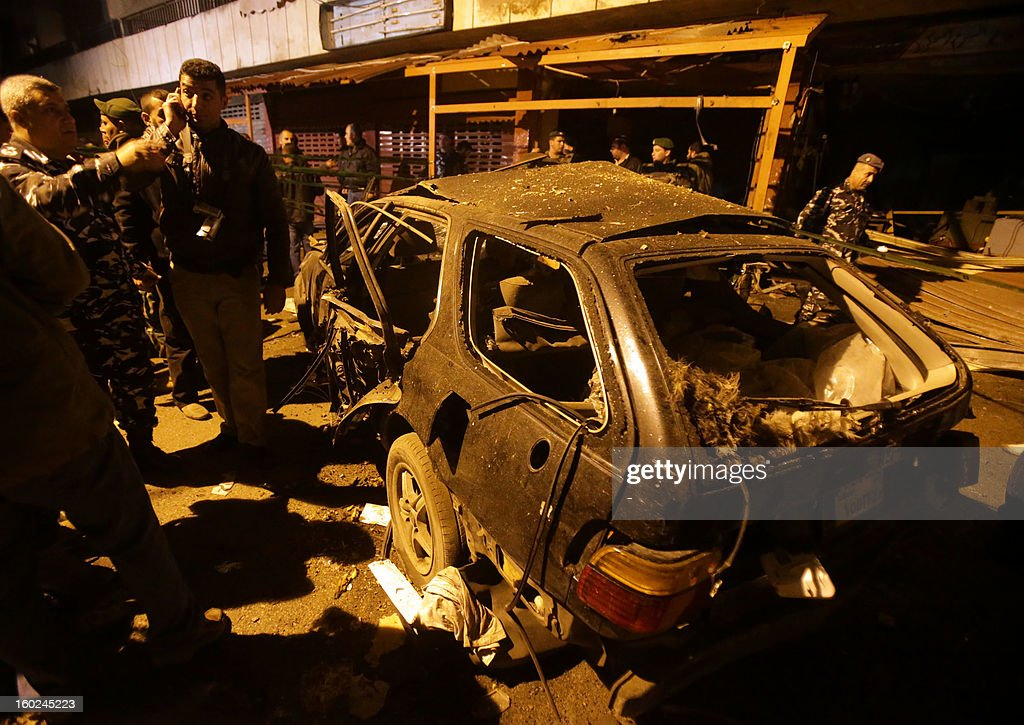 People gather around the wreckage of a car after a bomb placed under it exploded in a Shiite Muslim southern suburb of Beirut late on January 28, 2012, without causing casualties, a security source said. 'A bomb exploded under a car in Hay al-Sellom, causing only material damage,' the source told AFP on condition of anonymity. AFP PHOTO / STR