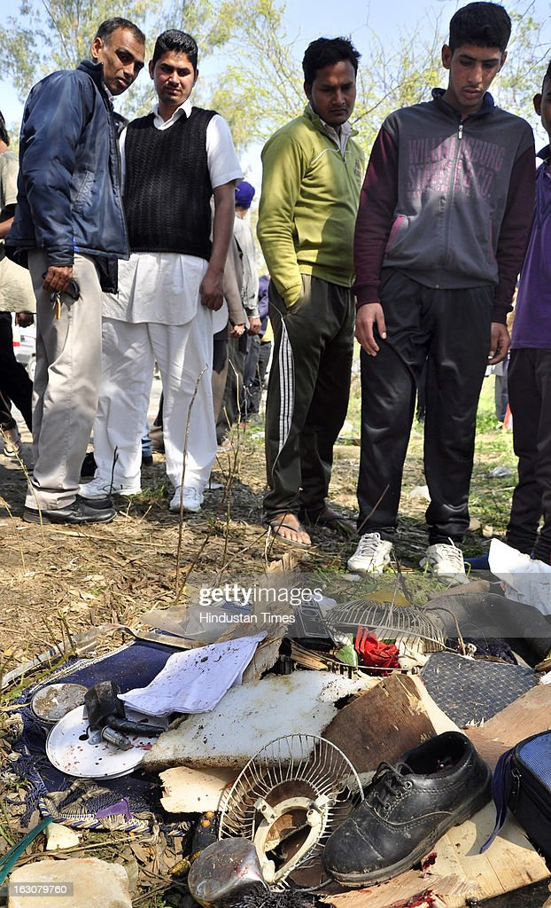 People gather around the wreckage of a school bus that collided with a truck laden with bricks on March 4, 2013 in Jalandhar, India. Atleast Twelve children and their driver were reportedly killed in the accident near Jaheera village in Lambhra, close to Nakodar town in the morning.