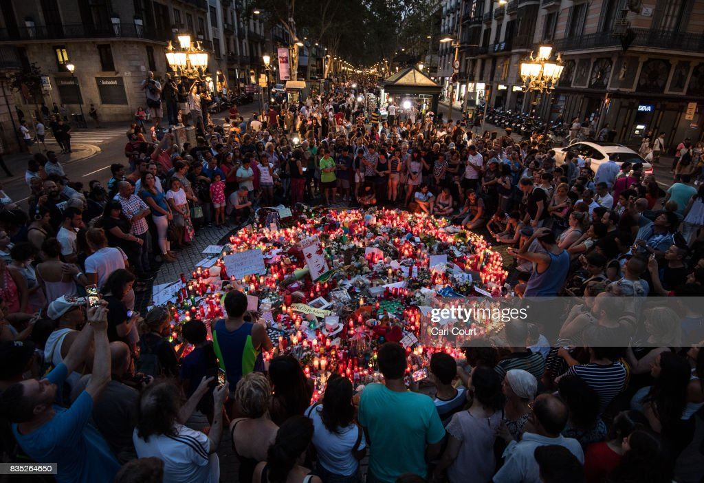 People gather around tributes laid on Las Ramblas near to the scene of yesterday's terrorist attack, on August 18, 2017 in Barcelona, Spain. Fourteen people were killed and dozens injured when a van hit crowds in the Las Ramblas area of Barcelona on Thursday. Spanish police have also killed five suspected terrorists in the town of Cambrils to stop a second terrorist attack.