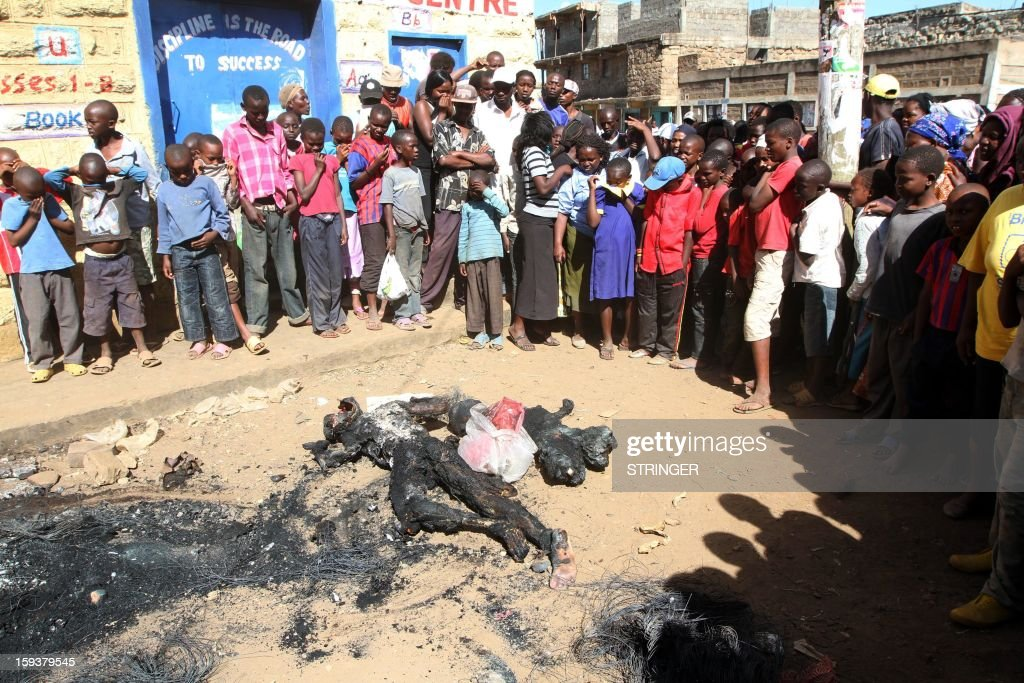 People gather around two charred bodies of men who were lynched on suspicion of being robbers, on January 12, 2013, in Nairobi's Dandora slum. Area residents said that for the last two weeks insecurity has been rife in the area as a group of criminals repeatedly attacked them with knives, stabbing and robbing them and today they managed to corner some of the gang's suspected members and set them alight.