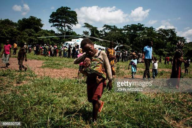 People gather as an helicopter carrying medical supplies and health workers specialised in Ebola virus arrive on June 11 2017 in Muma Two cases of...