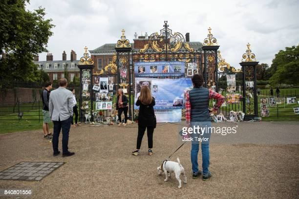 People gather as floral tributes photographs and messages sit outside an entrance gate to Kensington Palace ahead of the 20th anniversary of the...