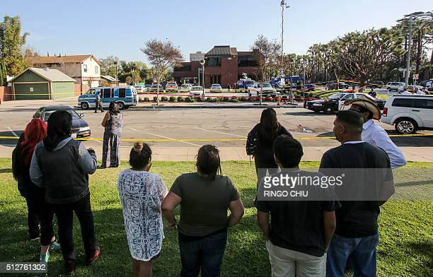 People gather as police officers investigate the scene near Pearson Park in Anaheim California February 27 after three counterprotesters were stabbed...