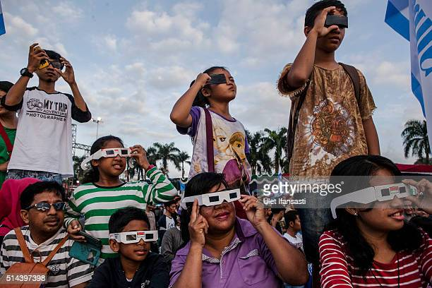 People gather as watch the total solar eclipse in Palembang city on March 9 2016 in Palembang South Sumatra province Indonesia A total solar eclipse...