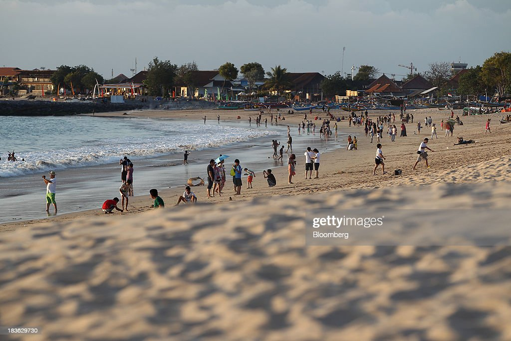 People gather at a beach in Jimbaran, Bali, Indonesia, on Saturday, Oct. 5, 2013. Indonesia's central bank kept its key interest rate unchanged after its most aggressive tightening cycle in almost eight years as inflation pressure eased. Photographer: SeongJoon Cho/Bloomberg via Getty Images