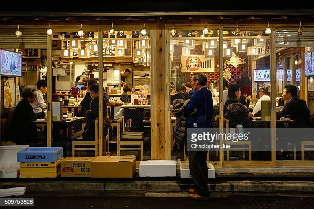 People gather at a local restaurant in downtown Tokyo on February 12 2016 in Tokyo Japan The Nikkei Stock Average finished 11% down for the week its...
