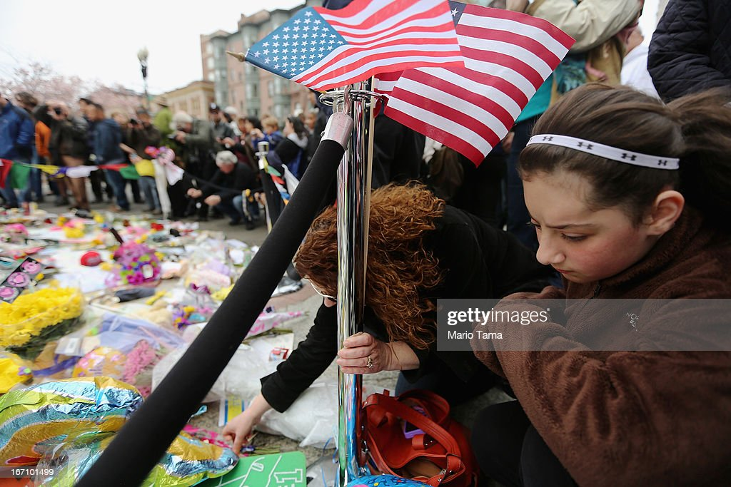 People gather at a makeshift memorial for victims near the site of the Boston Marathon bombings a day after the second suspect was captured on April 20, 2013 in Boston, United States. A manhunt for Dzhokhar A. Tsarnaev, 19, a suspect in the Boston Marathon bombing ended after he was apprehended on a boat parked on a residential property in Watertown, Massachusetts. His brother Tamerlan Tsarnaev, 26, the other suspect, was shot and killed after a car chase and shootout with police. The bombing, on April 15 at the finish line of the marathon, killed three people and wounded at least 170.