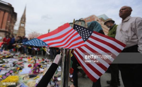 People gather at a makeshift memorial for victims near the site of the Boston Marathon bombings a day after the second suspect was captured on April...