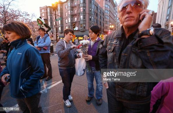 People gather at a makeshift memorial for victims near the site of the Boston Marathon bombings at the edge of the stillclosed section of Boylston...