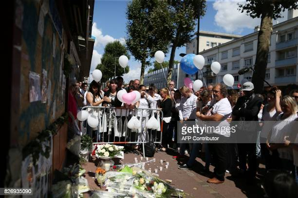 People gather at a makeshift memorial in front of the 'Au Cuba Libre' bar on August 6 in Rouen northwestern France in tribute to the 14 victims...