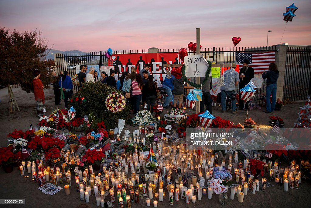 People gather at a makeshift memorial near the Inland Regional Center during the aftermath of a mass shooting that killed 14 people on Sunday...