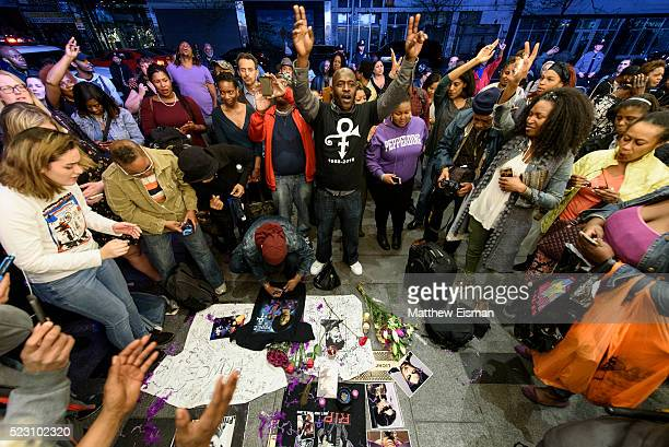 People gather at a makeshift memorial outside of the Apollo Theater dedicated to the musician Prince on April 21 2016 in New York New York Prince...