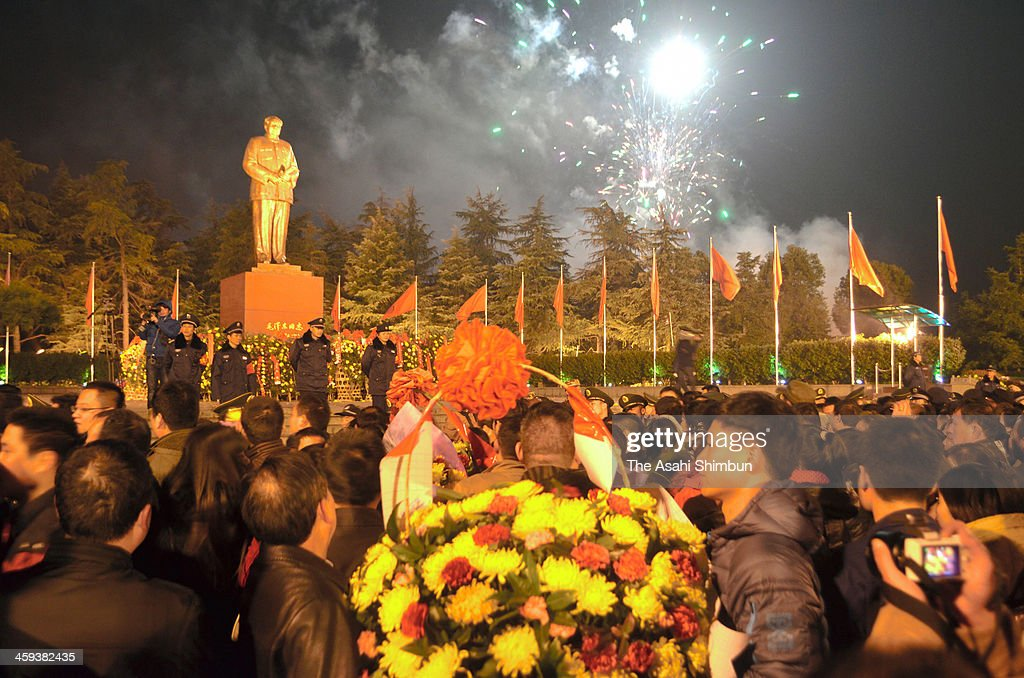 People gather at a square where the statue of Mao Zedong stands while fireworks explode to celebrate his 120th birthday on December 26, 2013 in Shaoshan, Mao's birthplace, Hunan, China.
