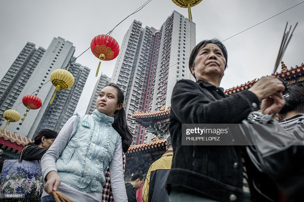 People gather at a Taoist temple in Hong Kong in Hong Kong on February 7, 2013. A stock market slide, escalated conflict between Japan and China and more Gangnam-styled success for South Korean singer Psy will shape the incoming Year of the Snake, say Asian soothsayers. February 10 marks the first day of the Lunar New Year across the region. AFP PHOTO / Philippe Lopez