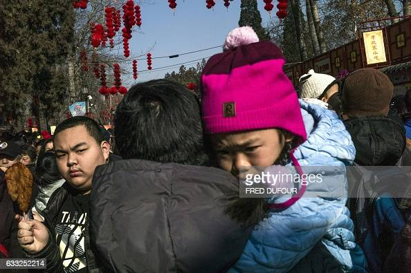 People gather at a temple fair in Ditan park during Lunar New Year celebrations in Beijing on February 1 2017 The Lunar New Year fell on January 28...