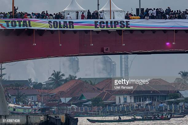 People gather at Ampera Bridge to watch a total solar eclipse in Palembang city on March 9 2016 in Palembang South Sumatra province Indonesia A total...