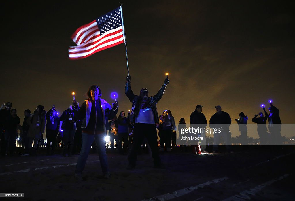 People gather at Midland Beach during a Light the Shore vigil in rememberance of the first anniversary of Superstorm Sandy on October 29, 2013 in the Staten Island borough of New York City. Commemorative events took place across the northeast one year after the storm devestated much of the coastline.