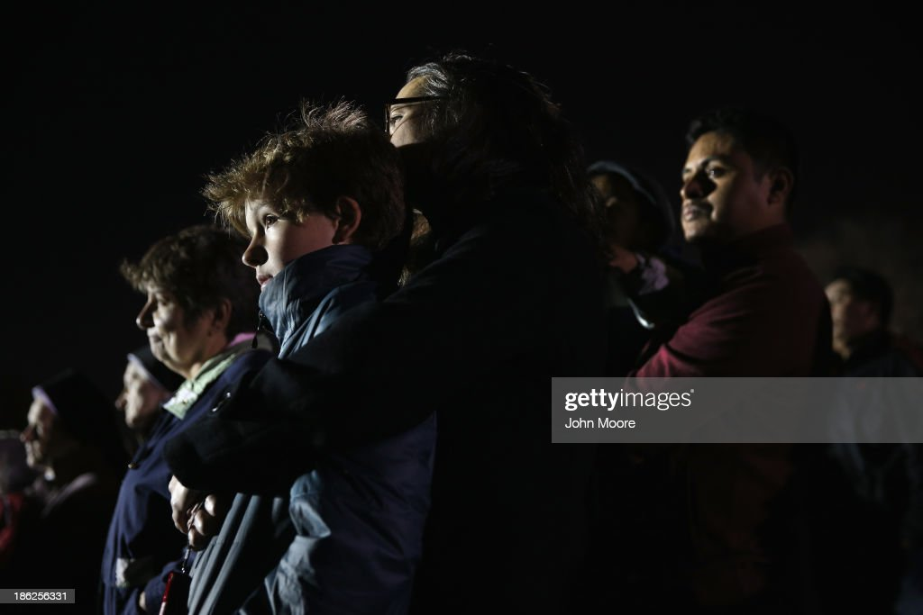 People gather at Midland Beach during a 'Light the Shore' vigil in rememberance of the first anniversary of Superstorm Sandy on October 29, 2013 in the Staten Island borough of New York City. Commemorative events took place across the northeast one year after the storm devestated much of the coastline.