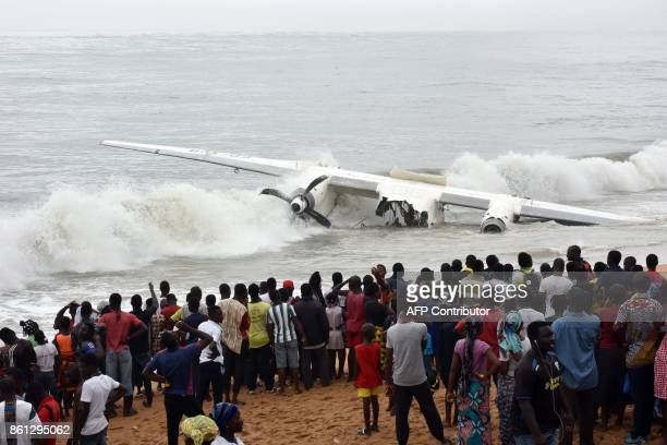 People gather at the beach of PortBouet in Abidjan on October 14 2017 to look at the the wreckage of a cargo plane that crashed off Ivory Coast...