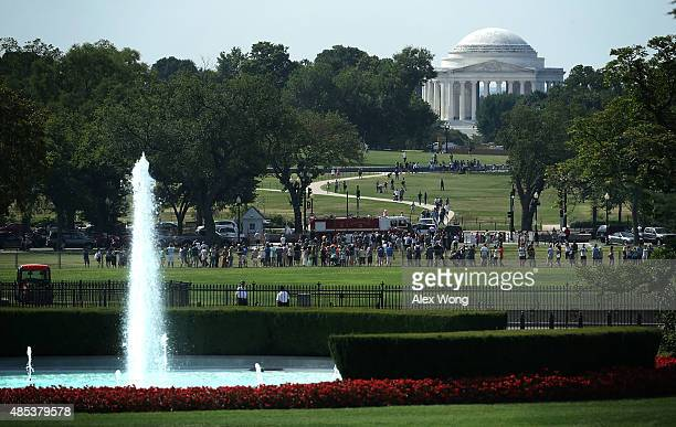 People gather at the Ellipse to watch the departure of US President Barack Obama aboard the Marine One from the White House August 27 2015 in...