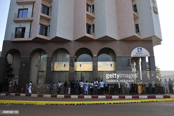 People gather at the entrance the Radisson Blu hotel in Bamako on November 24 in tribute to the victims four days after the deadly terrorist attack...
