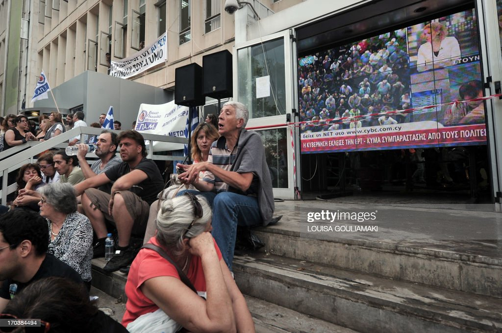 People gather at the ERT headquarters in an Athens suburb on June 12, 2013, a day after a shock decision by the government to shut down the state broadcaster's operations with immediate effect, a move affecting nearly 2,700 jobs. The announcement comes after months of work stoppages by ERT employees in opposition to plans to restructure the broadcaster as demanded by debt-laden Greece's troika of international creditors. The Greek government said today it will reorganise the state broadcasting company after it abruptly pulled the plug on ERT as part of its austerity drive...