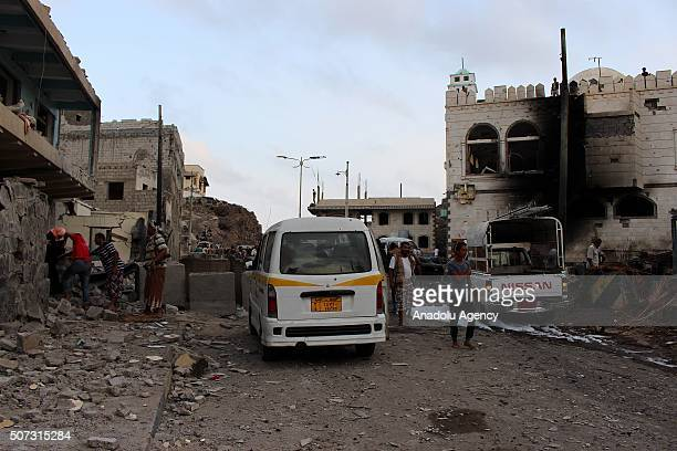People gather at the explosion site close to Presidential residence after a carbomb attack in Aden Yemen on January 28 2016