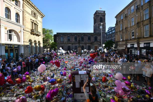 People gather at the flowers and messages of support in St Ann's Square in Manchester northwest England on May 26 placed in tribute to the victims of...
