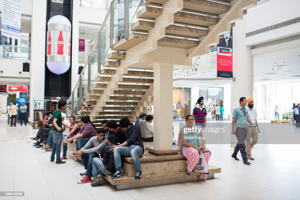 People gather at the foot of a staircase at the AlphaOne shopping mall in Amritsar, India, on Thursday, May 9, 2013. India's consumer price index (CPI) for April rose 9.39 percent year on year, the Central Statistics Office said in a statement on its website. Photographer: Brent Lewin/Bloomberg via Getty Images