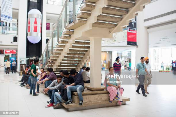 People gather at the foot of a staircase at the AlphaOne shopping mall in Amritsar India on Thursday May 9 2013 India's consumer price index for...